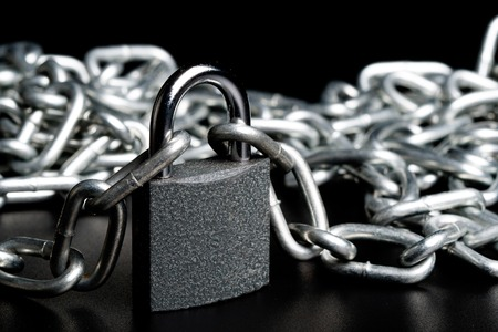 steel chain on the lock lying on a black background, glare on metal, pendant lock and chain