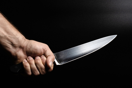 tightly clenched knife with large blade kitchen chef knife, black background