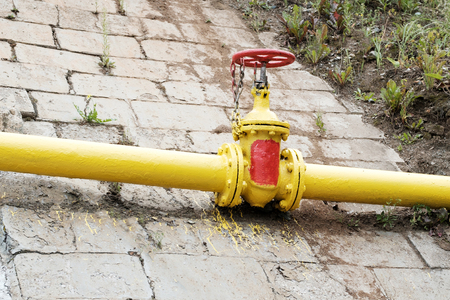 yellow pipe on the background of a large stone slab, valve yellow gas equipment