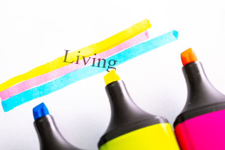 written life and circled with different colored markers, yellow red blue, markers out of focus in the foreground