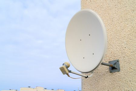 a satellite dish for receiving TV signal is bolted to the white wall, Russia residential sector