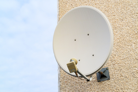 old satellite dish mounted on the wall of the house, the wall of the house of small stone chips, satellite TV