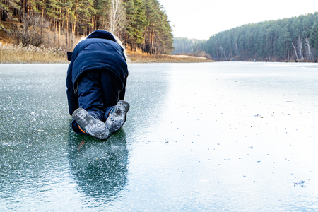 on all fours crawling child on the ice is very slippery, the winter ice