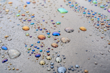 drops of water on the bitumen surface, mixing oil and water gave colored stains on the water