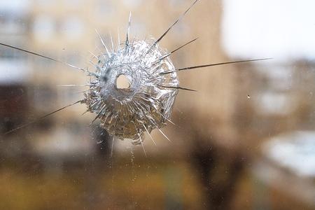 cracks in the glass shot mark, bullet mark on the window.