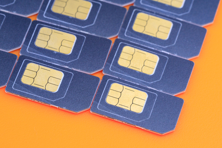 SIM cards on an orange background form a corner.