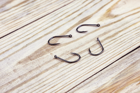 on the texture of wood are four black fishing hooks, fishing tackle 版權商用圖片