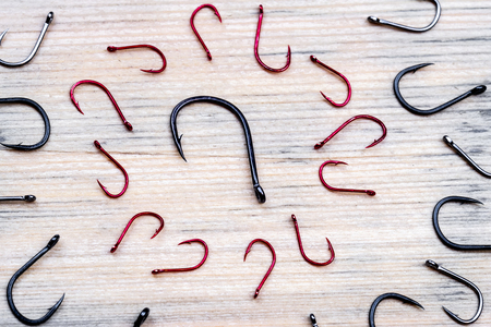 top view of the fishing hooks, the surface of the wood, a large hook around which the red hooks to a smaller size 写真素材