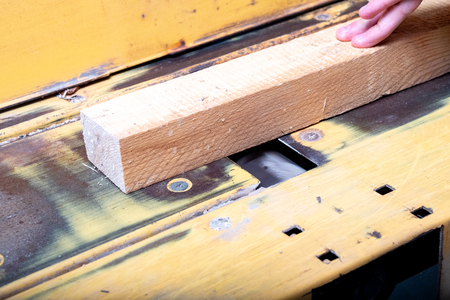 the wooden bar is treated on an electric jointer, hands are not protected Stockfoto