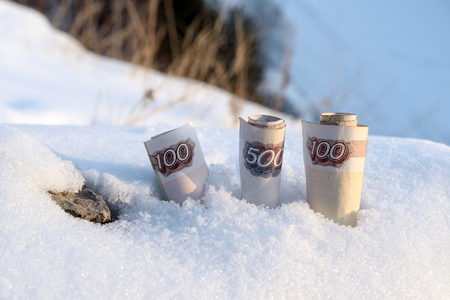 in the snow by the stone there are three rolled banknotes, the snowy period of winter Banco de Imagens