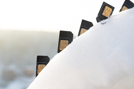 SIM card in the curve curve of of snow inserted in the ascending ladder, the background sky in the winter