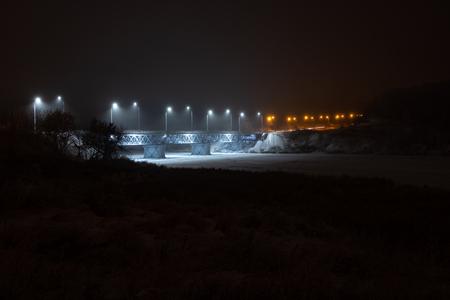 brug over de rivier 's nachts verschillende kleuren lichten op de brug en mist