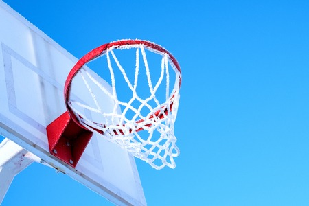 winter basketball in Russia blue sky and frozen ring and net on the basket 스톡 콘텐츠