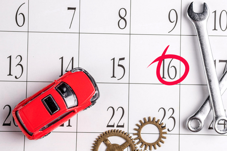 red car and a set of wrenches on the calendar background, the date is circled in red