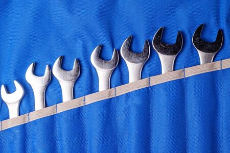 wrench vertical position in a row all tools are inserted into their places on a blue fabric background