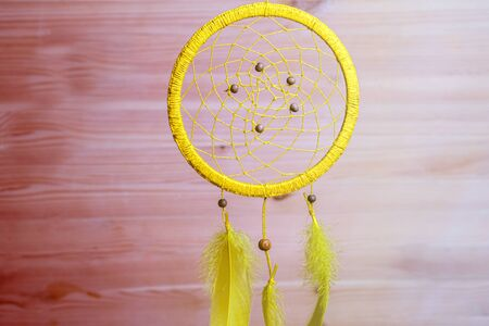 a homemade Dreamcatcher hanging on a brown background, coloured plank of wood 写真素材