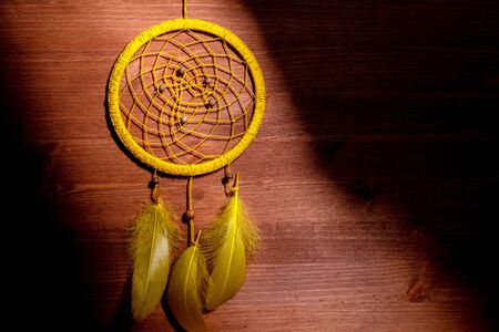 round yellow dream catcher on the side black strips amulet guarding the dreams on the background of wooden wall