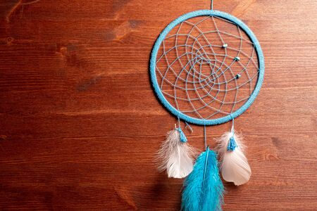 Dreamcatcher blue with feathers of birds on the ropes homemade amulet on the wall of wood 写真素材