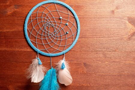 Dreamcatcher with blue and white feathers on a dark wooden surface handmade background