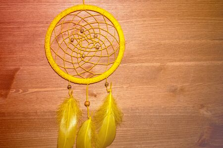 round homemade amulet for catching dreams woven from threads on a wooden surface 写真素材