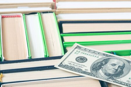 a hundred dollar bill lying on books with thick spines of different colors