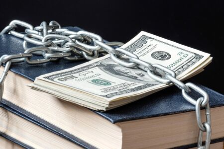 a stack of books on a dark background is covered by a chain under which there is also a pack of money Stok Fotoğraf