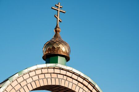 cross on the dome of the Orthodox Church in Russia against the blue sky