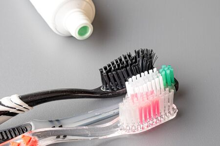 an open tube of green toothpaste is placed in front of three toothbrushes. family toothpaste and tooth cleaning