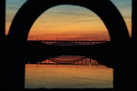 view of the railway bridge which is located across the river at sunset, through the arch. foreground silhouette out of focus