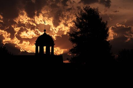 silhouettes of trees and heads with columns against the sunset sky. Russia Kamensk-Ural small town