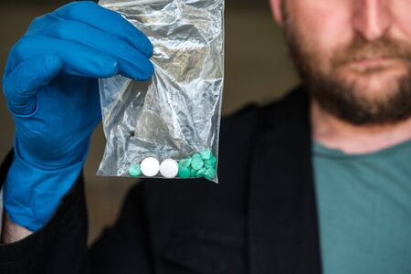 a bearded man in blue rubber gloves holds a bag of drugs in his hand. the drugs found by criminalists as a result of searches in rooms Reklamní fotografie