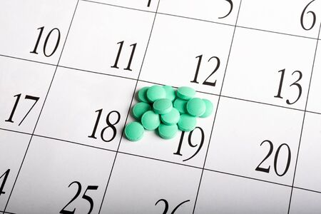 green pills lying on the calendar on one date a bunch of. suicide by eating multiple pills in one day