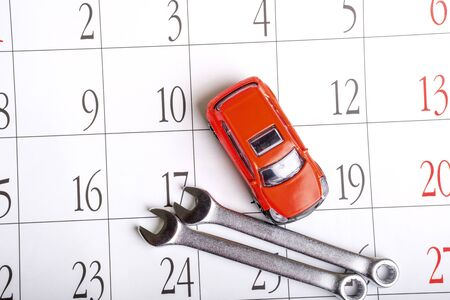 red toy car top view and wrenches on the calendar sheet. routine maintenance and inspection of vehicles on schedule 版權商用圖片
