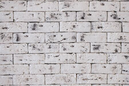 the texture of a white brick wall of large artificially aged bricks with flaws Stock Photo