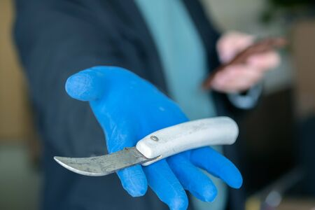 knife with a curved blade in the hands of blue gloves background room. a blue-gloved homicide specialist holds out a knife showing evidence. Archivio Fotografico