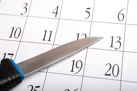 an old secondhand knife on a calendar sheet with dates. plan a murder with a knife