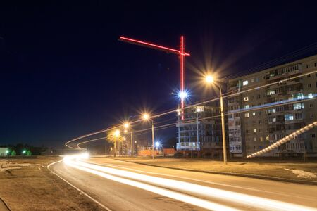 at night in the city a multi storey house behind which there is a tower crane and the whole structure is illuminated by a passing car traces of headlights