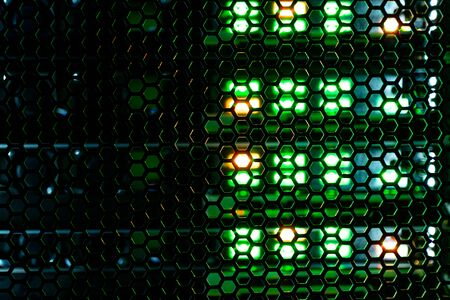 hexagonal mesh texture of metal behind which the indicator lights of the equipment. abstract background with hexagon texture glow through them Фото со стока