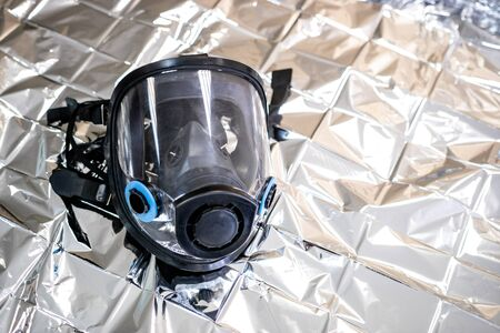 the shiny surface of the crumpled foil on it is a black gas mask. personal protective equipment Foto de archivo