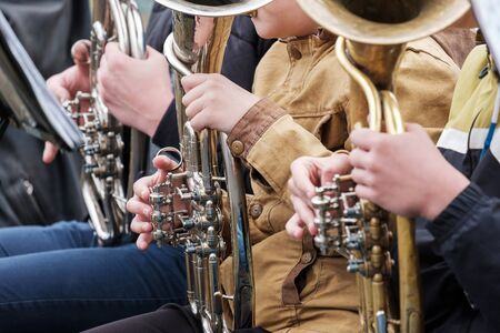 street musicians playing wind instruments outdoors in outerwear. playing for the sake of earning street musicians on the horns Stock Photo