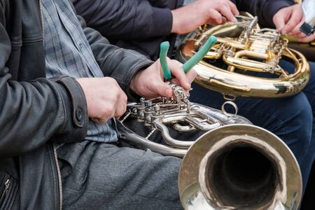 a street musician repairs a broken musical instrument on the spot. street musicians are forced to repair their own instruments Zdjęcie Seryjne