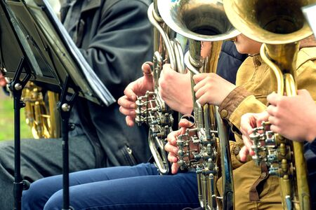 hands playing street musicians on wind instruments