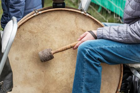 big drum and drummer sitting next to him with a stick outside. street musician with street clothes