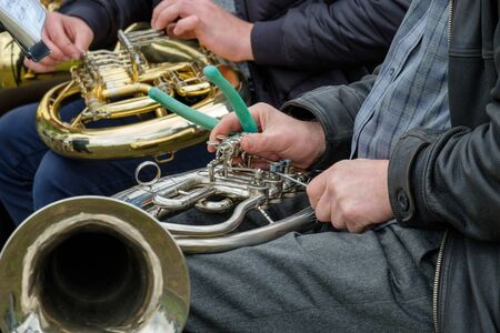 repair faulty horn musical wind instrument on the street during the performance. pliers and a screwdriver in the hands of a street musician have to do everything yourself