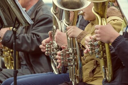 close - up of the hands of street musicians on the keys of the horn. a number of street musicians sitting in street clothes
