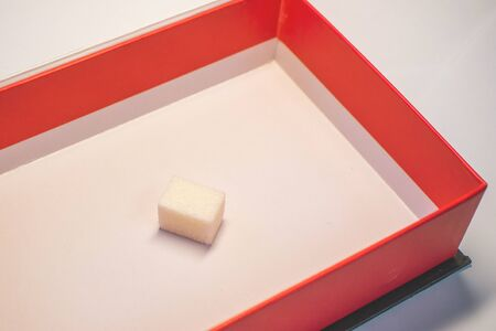 a sugar cube in a box with red edges. sweet cube calorie as a gift