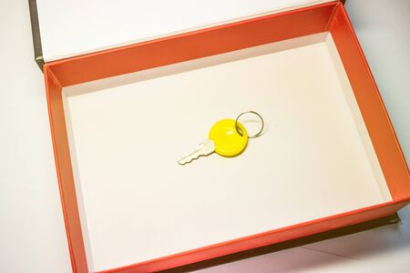 a small yellow key in a cardboard box with a red border. the key to the cell as a gift