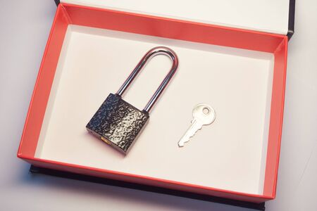 padlock and the keys to it in a box with red cardboard margins. the lock from the door a gift