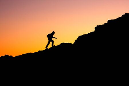 photo in a dark key of a man climbing a mountain. a man illuminated from behind by the sun climbs up the mountain Stock fotó