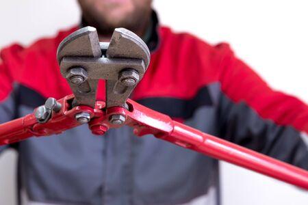 Mann in Arbeitskleidung, der in beiden Händen eine große Schere zum Schneiden der Scherenstangen hält, wird auf die Kamera gerichtet. Angestellter im Geschäft